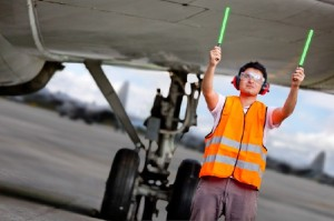 Air traffic controller holding light signs at the airport